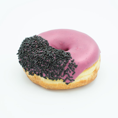 Ring doughnut with light purple hibiscus flavored icing and chocolate sprinkles on the left half
