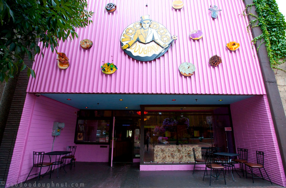 Store front of Voodoo Doughnut in Eugene with pink exterior logo sign and large doughnuts