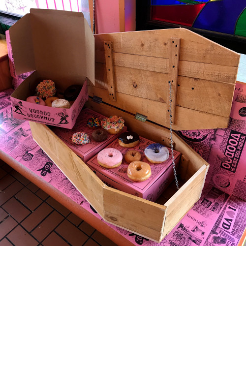 Voodoo Doughnut Coffin of Doughnuts open on a pink bench