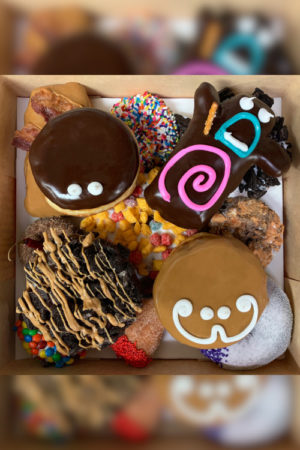 A top down view of a dozen Fryer Flyer doughnuts including a Bacon maple bar and Voodoo Doll