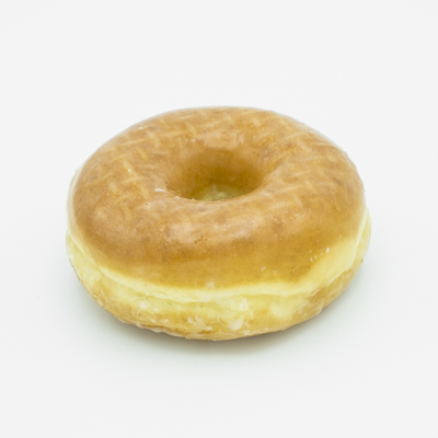 Image of a glazed ring yeast doughnut shown close up and from the side.