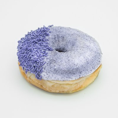 Image of the Grape Ape Doughnut -- raised yeast doughnut with vanilla frosting, then coated with grape dust, and lavender sprinkles on one side, and shown up close from a side angle.
