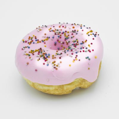 Image of the Homer Doughnut, a raised yeast ring doughnut, dipped in pink strawberry flavored icing, sprinkled with colorful non-pareils; shown up close from the side.