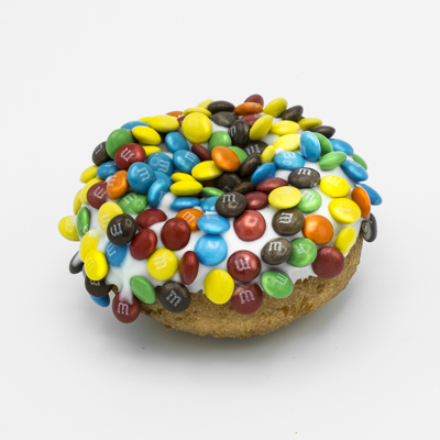 Image of a plain cake doughnut with vanilla frosting and covered with mini M&Ms