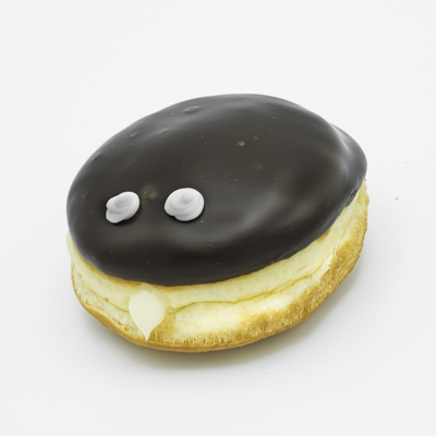 Image of a Portland Cream Doughnut -- a Bavarian cream round doughnut with chocolate frosting and two eyes of white frosting; shown from the side and up close.