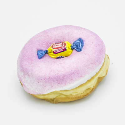 Image of the Voodoo Bubble Doughnut which is a raised yeast doughnut with vanilla frosting, dipped in bubble gum dust, and with a piece of wrapped bubble gum in the doughnut hole; shown from a side angle and up close.