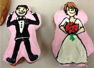 Two Doughnuts shaped and frosted to look like a traditional groom and bride