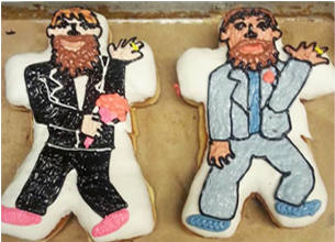 Two doughnuts shaped and frosted to look like two men in suits