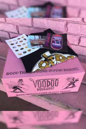 Pink doughnut box with black 3-D logo t-shirt, with some stickers and postcards