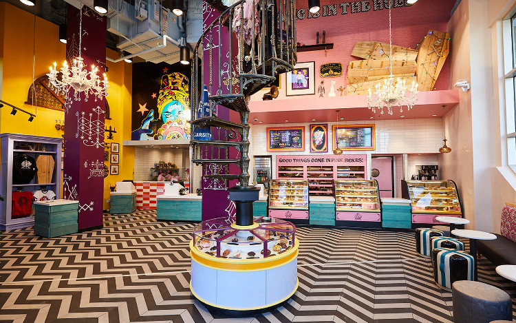 Interior of shop - colorful pink counter, seating area, and central spiral staircase