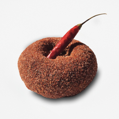 Chocolate cake doughnut dusted with cinnamon, cayenne pepper, and topped with a dried red chili pepper..